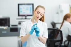 Professionele arts met medische spuit in handen, die klaar voor injectie in modern laboratorium worden stock afbeelding