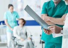Professionele artsen die de geduldige röntgenstraal van ` onderzoeken s stock afbeelding