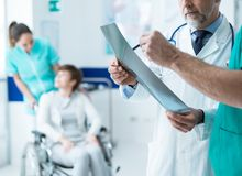Professionele artsen die de geduldige röntgenstraal van ` onderzoeken s stock fotografie
