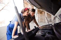 Professionele autovrouwenwerktuigkundige en man reparatieauto in openlucht royalty-vrije stock fotografie