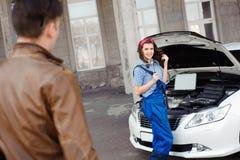 Professionele autovrouwenwerktuigkundige en man reparatieauto in openlucht royalty-vrije stock foto's