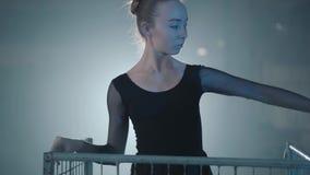 Professionele ballerina die in zwarte kleding in de studio binnen de blauwe kooi in schijnwerper op een zwarte achtergrond dansen stock video