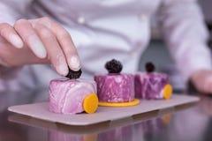 Professionele banketbakker die hoofdklasse bij het verfraaien van desserts geven stock foto's