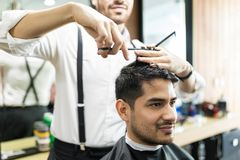 Professionele Barber Giving Haircut To Male in Winkel stock foto's