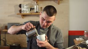 Professionele barista die gestoomde melk gieten in koffiekop die latte art. maken stock videobeelden