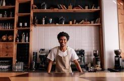 Professionele barista die zich bij koffieteller bevinden royalty-vrije stock afbeeldingen