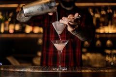 Professionele barman die Kosmopolitisch van een schudbeker pourring aan royalty-vrije stock afbeelding
