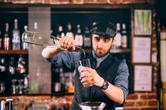 Professionele barman gietende rum in cocktails bij bar, bar of restaurant royalty-vrije stock afbeelding