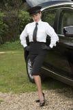 Professionele bestuurder die zich met handen op heupen door haar auto bevinden stock fotografie