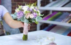 Professionele bloemist die het boeket van het bloemhuwelijk in bloemenontwerpstudio voorstellen met vrije exemplaarruimte stock afbeelding