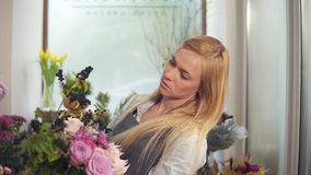 Professionele blonde vrouwelijke bloemenkunstenaar die mooi huwelijksboeket schikken bij bloemwinkel Met de hand gemaakte Florist stock footage