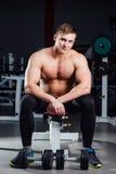 Professionele bodybuilderzitting op de bank, die tussen oefeningen met domoren bij gymnastiek rusten groot Royalty-vrije Stock Foto's