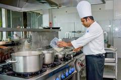 Professionele chef-kok die ingrediënten toevoegen aan omlete stock afbeelding