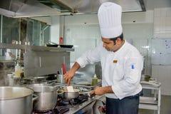 Professionele chef-kok die omlete zich op de koekepan mengen stock afbeelding