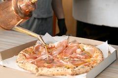 Professionele chef-kok gietende olijfolie op Italiaanse oven gebakken pizza in restaurant royalty-vrije stock fotografie