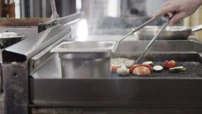 Professionele chef-kok kokende vlees en groenten op a stock videobeelden