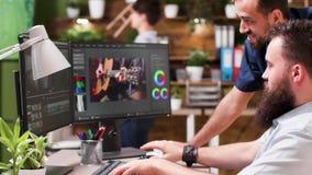 Professionele colorist en videoredacteur die aan nieuwe muziekvideo werken stock videobeelden