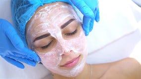 Professionele cosmetologist en dermatoloog die gezichtsmasker toepassen bij vrouwengezicht en gezichtsmassage doen Procedures voo stock footage