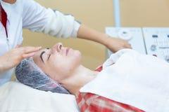 Professionele cosmetologist maakt tot procedure aan mooi meisje in de kosmetiekkabinet royalty-vrije stock afbeeldingen