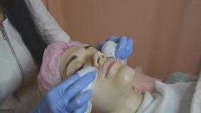 Professionele cosmetologist stemt het gezicht van de vrouw gebruikend katoenen spons stock videobeelden