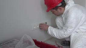 Professionele de contactdoosafzet van de arbeiders opzettende muur bij de nieuwe vlakke woningbouw stock video