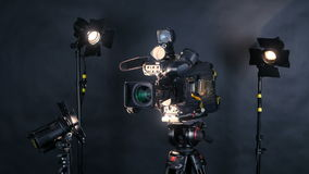 Professionele digitale videocamera, camcoder geïsoleerd op zwarte achtergrond in TV-srudio stock videobeelden
