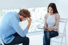 Professionele ervaren therapeut die onderaan de symptomen nota nemen van Stock Foto