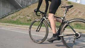 Professionele fietser berijdende fiets uit het zadel Zij dichte omhooggaande mening van beenspieren in motie Pedalingstechniek op stock videobeelden