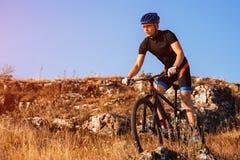Professionele Fietser die de Fiets berijden in Rocky Trail Sportman in de helm en de zonnebril Royalty-vrije Stock Foto's