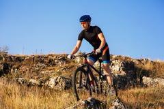 Professionele Fietser die de Fiets berijden in Rocky Trail Sportman in de helm en de zonnebril Stock Foto
