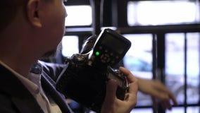 Professionele foto die binnen schieten De fotograaf neemt beelden met een digitale camera DSLR Photosession stock footage