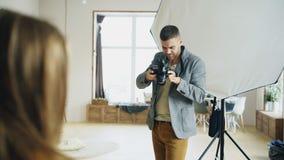 Professionele fotograaf die foto's van model op digitale camera nemen die in fotostudio werken Stock Afbeelding