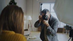 Professionele fotograaf die foto's van model op digitale camera nemen die in fotostudio werken royalty-vrije stock afbeelding