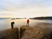 Professionele fotograaf en wandelaar die in wilde aard met een digitale camera en een driepoot schieten stock foto