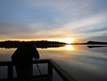 Professionele Fotograaf Silhouette met Driepoot tijdens Zonsondergang over Mooi Meer met Bewolkte Hemel op achtergrond Royalty-vrije Stock Fotografie