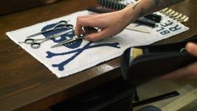 Professionele getatoeeerde kapper die een nieuw kapsel geven aan zijn cliënt in een herenkapper stock videobeelden