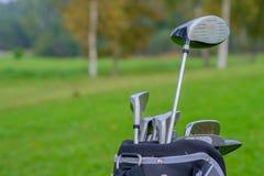 Professionele golfclubs in een leerbagage bij zonsondergang Stock Afbeeldingen