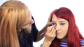 Professionele grimeurkleurstoffen de ogen van het model de stilist schildert wimpers stock videobeelden