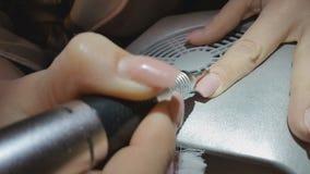 Professionele hardwarepedicure gebruikend elektrische machine De manicure grinded de spijkers van het meisje in de spijkersalon stock videobeelden