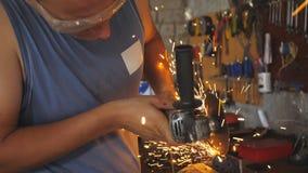 Professionele hersteller of mechanisch arbeiders zagend metaal met een cirkelzaag in garage Het volwassen lassers scherpe staal g stock videobeelden
