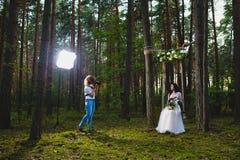 Professionele huwelijksfotograaf die stroboscoop met behulp van en softbox om beelden te maken stock foto