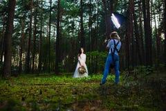 Professionele huwelijksfotograaf die stroboscoop met behulp van en softbox om beelden te maken stock fotografie