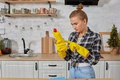 Professionele jonge vrouw die rubber beschermende gele handschoenen dragen die flessenreinigingsmachines in de keuken houden stock afbeeldingen