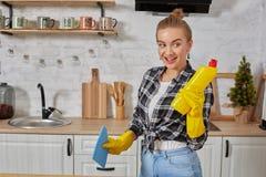 Professionele jonge vrouw die rubber beschermende gele handschoenen dragen die flessenreinigingsmachines in de keuken houden stock fotografie