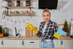 Professionele jonge vrouw die rubber beschermende gele handschoenen dragen die flessenreinigingsmachines in de keuken houden stock afbeelding