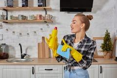 Professionele jonge vrouw die rubber beschermende gele handschoenen dragen die flessenreinigingsmachines in de keuken houden royalty-vrije stock afbeeldingen