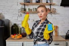 Professionele jonge vrouw die rubber beschermende gele handschoenen dragen die flessenreinigingsmachines in de keuken houden royalty-vrije stock afbeelding