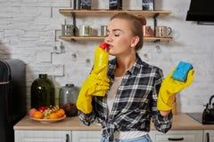Professionele jonge vrouw die rubber beschermende gele handschoenen dragen die flessenreinigingsmachines in de keuken houden royalty-vrije stock foto