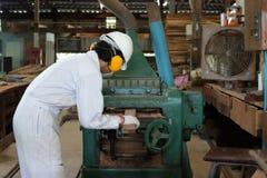 Professionele jonge werknemer in het witte veiligheid eenvormige werken met schavende machine in fabriek stock foto's