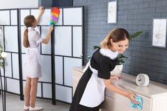 Professionele kamermeisjes in het eenvormige schoonmaken stock afbeelding